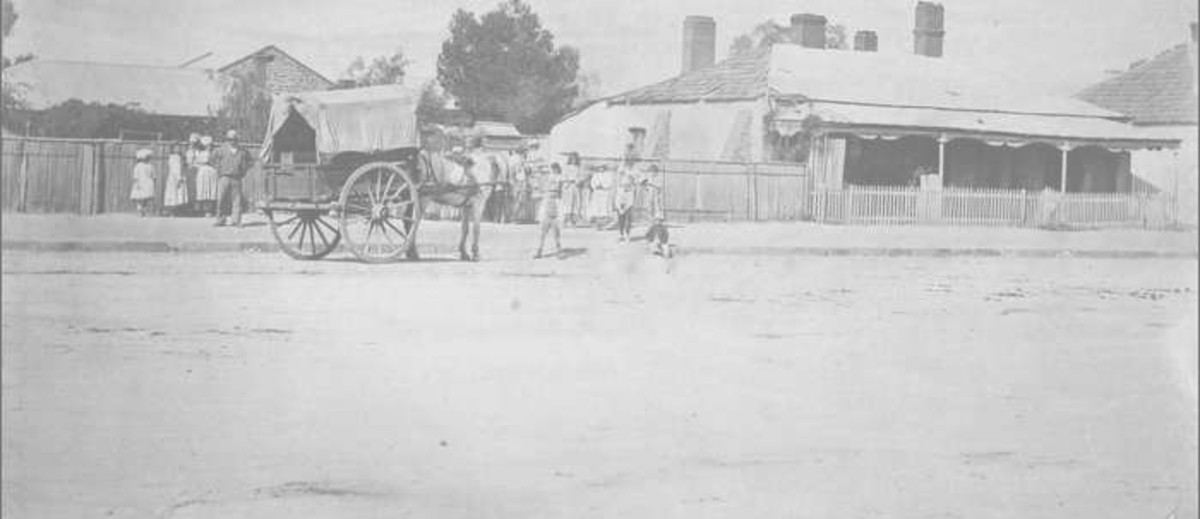 Image: a group of men, women and children in late 19th century clothing gather around a horse drawn cart on a dirt road lined by single storey cottages.