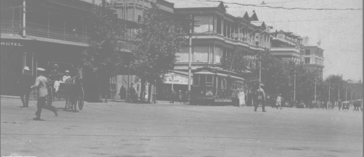 Image: a series of three storey buildings line one side of a wide city street. Between the buildings and the road is a line of trees. Travelling along the street are horse-drawn vehicles, motor cars and an electric tram, as well as people in 1920s clothes