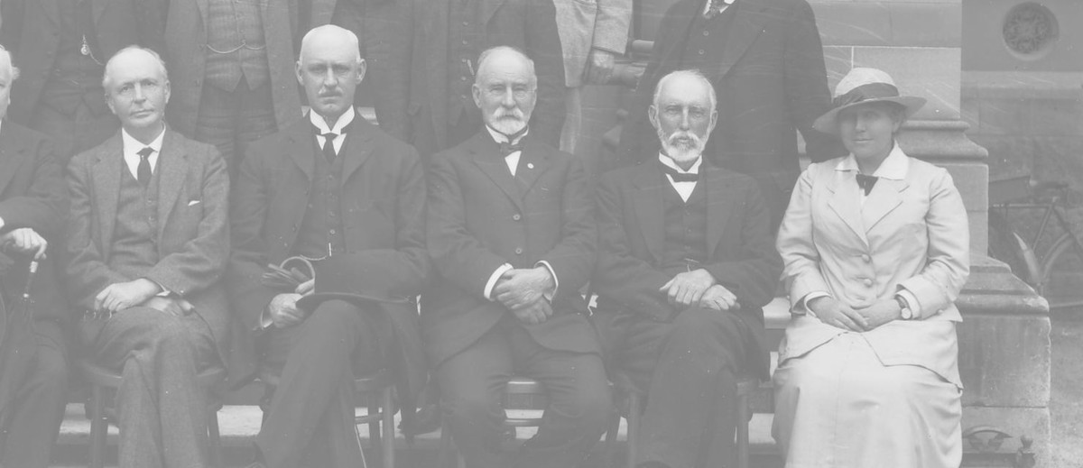 Image: A group of men in Edwardian attire pose for a photograph. A single woman in a light-coloured outfit is seated among their ranks in the front row