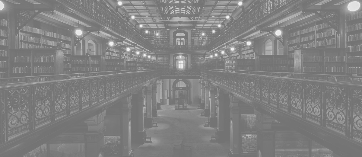 Image: The interior of a large, three-storey Victorian-era library. A large skylight in the roof illuminates the building's three floors of bookshelves and museum exhibits