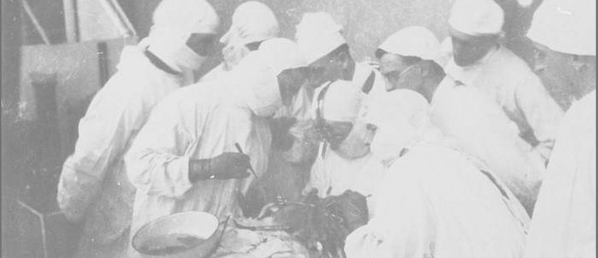 Image: A group of surgeons and medical technicians in white surgery gowns surround a patient on an operating table. Three men closest to the patient are performing an operation