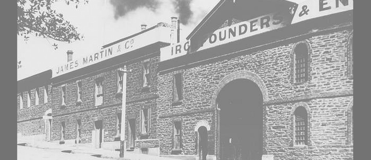 Image: A large complex of stone two-storey buildings next to a street. A sign on the front of the building reads 'James Martin & Co., Iron Founders'