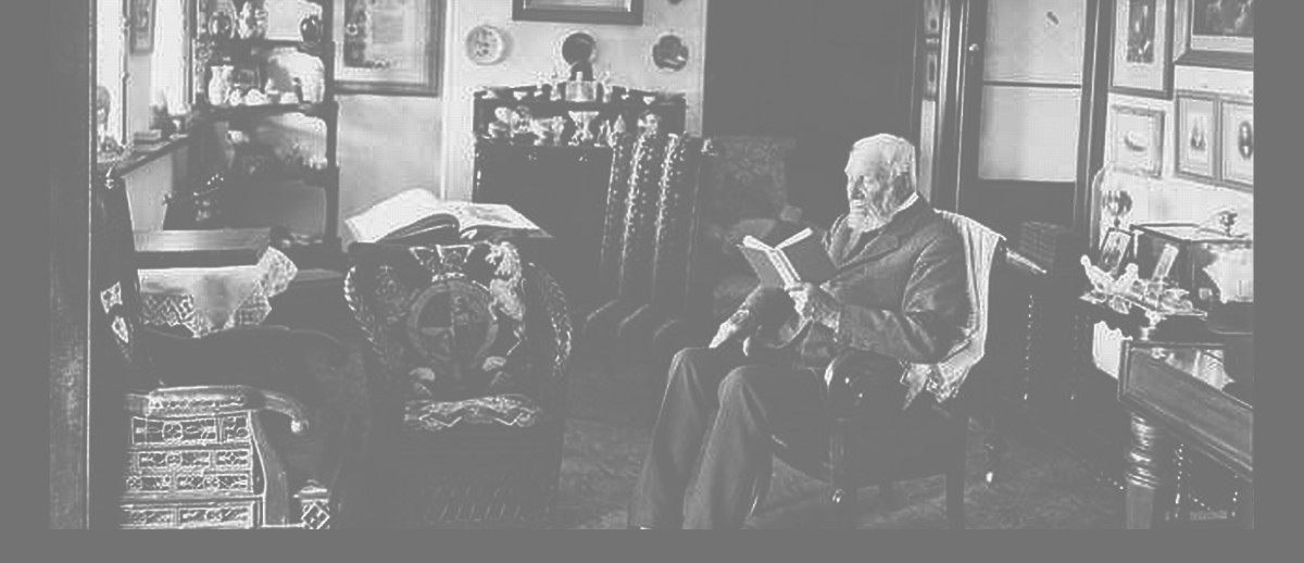 Image: An elderly bearded man sits in a chair and reads a book. The room contains a variety of furnishings and several paintings hang on the walls