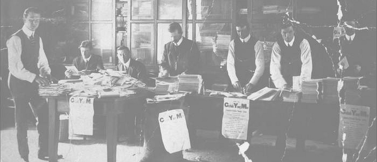 """Images: A group of men stand and sit behind a long table covered with books and papers. Signs on the table read 'C.Y.M.', an acronym for """"Catholic Young Men's"""""""
