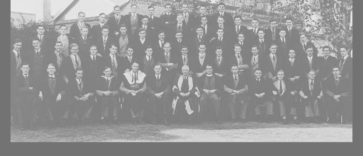 Image: A group of men in mid-20th century suits and academic gowns pose for a photograph outside a large, singles-storey stone building
