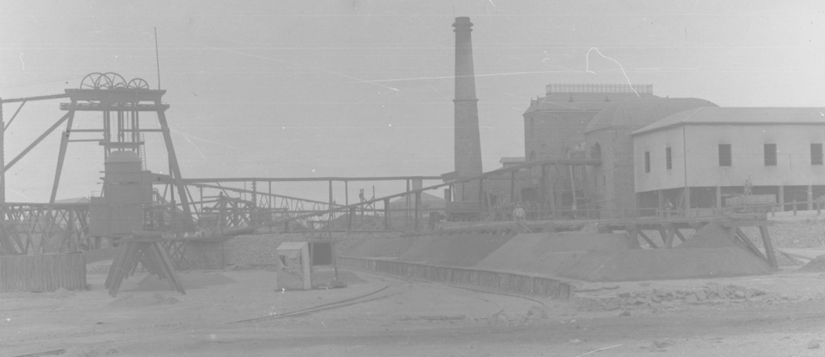 Image: A cylindrical brick chimney is surrounded by a number of buildings and industrial machinery