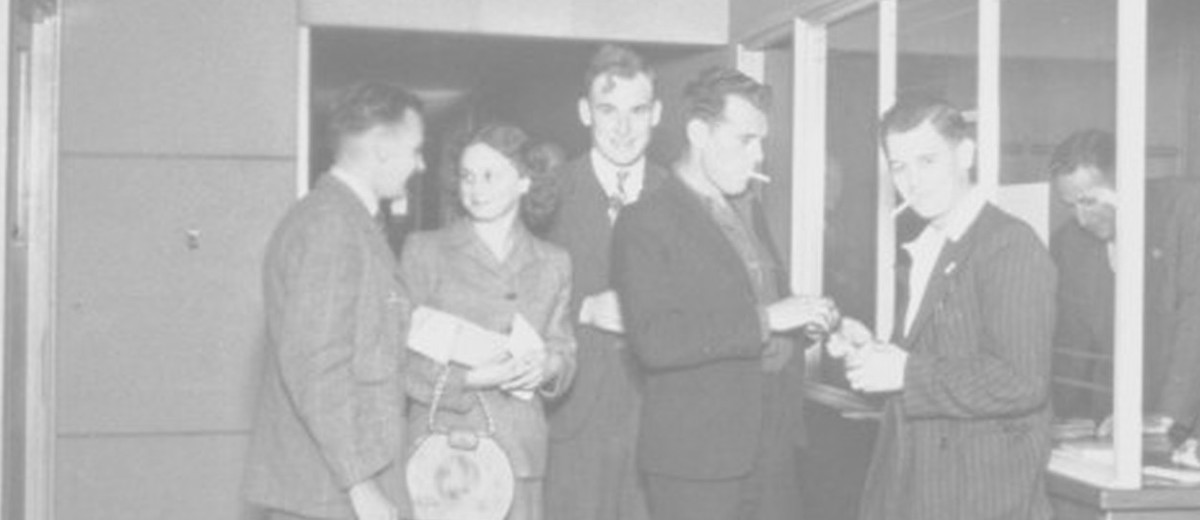 Image: six men and a woman in 1940s era dress stand around a reception desk while a seventh man leans on the desk, writing, behind a glass barrier. In the foreground a second woman in a hat sits looking at the group.