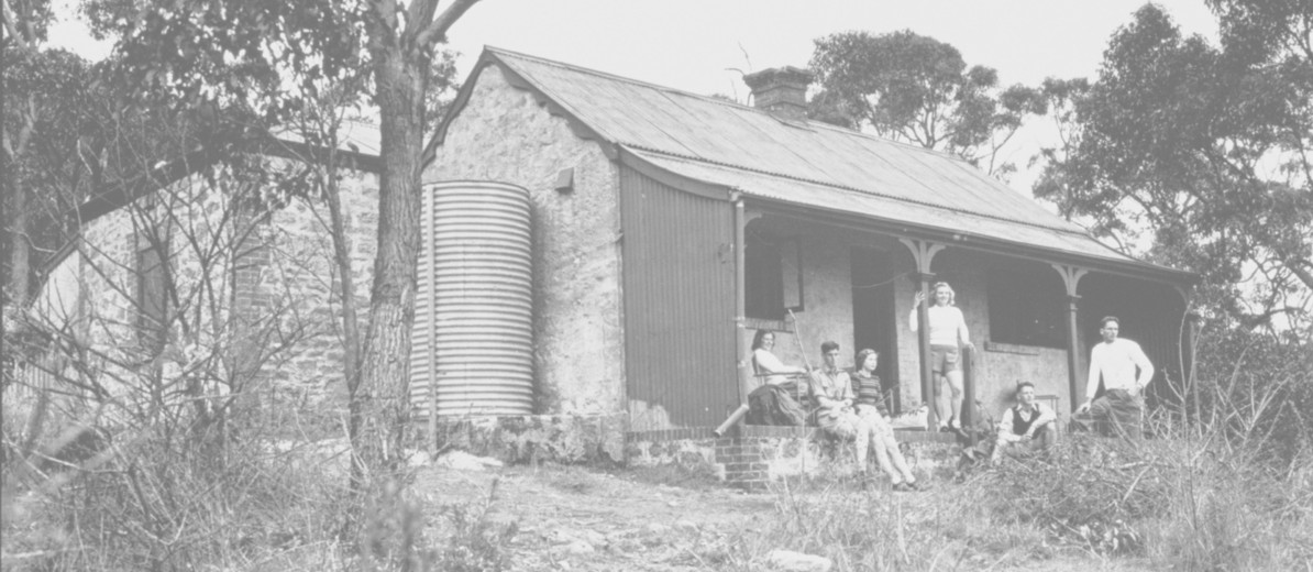 Image: A small group of young men and women sit on the porch of an old stone cottage. The cottage is surrounded by trees and scrub