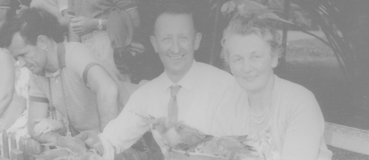 Image: a man and woman looking at camera while feeding pigeons