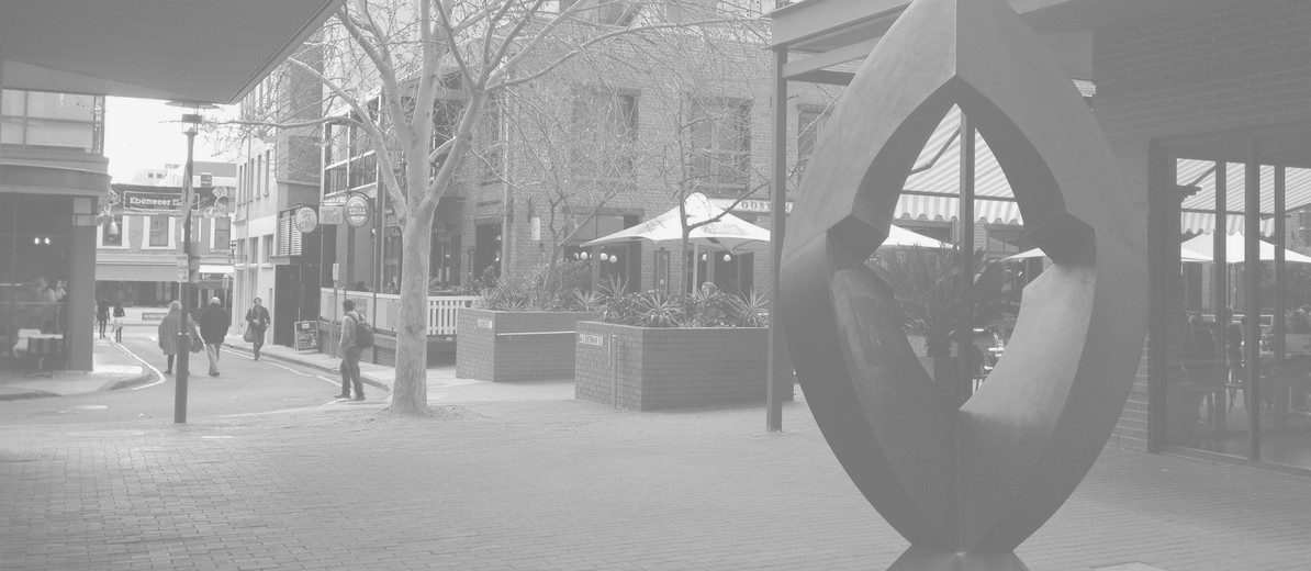 Image: steel quadrangle-shaped sculpture with rounded edges and a geometric hole in the middle in front of a brick courtyard with restaurants' patios