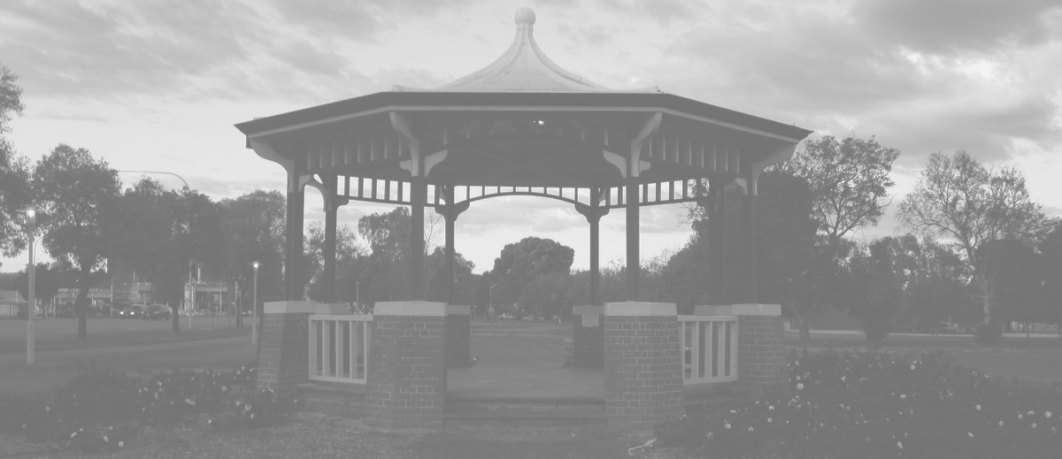 Image: A green and white gazebo with red brick footers stands in a park. A street with cars is visible in the left background