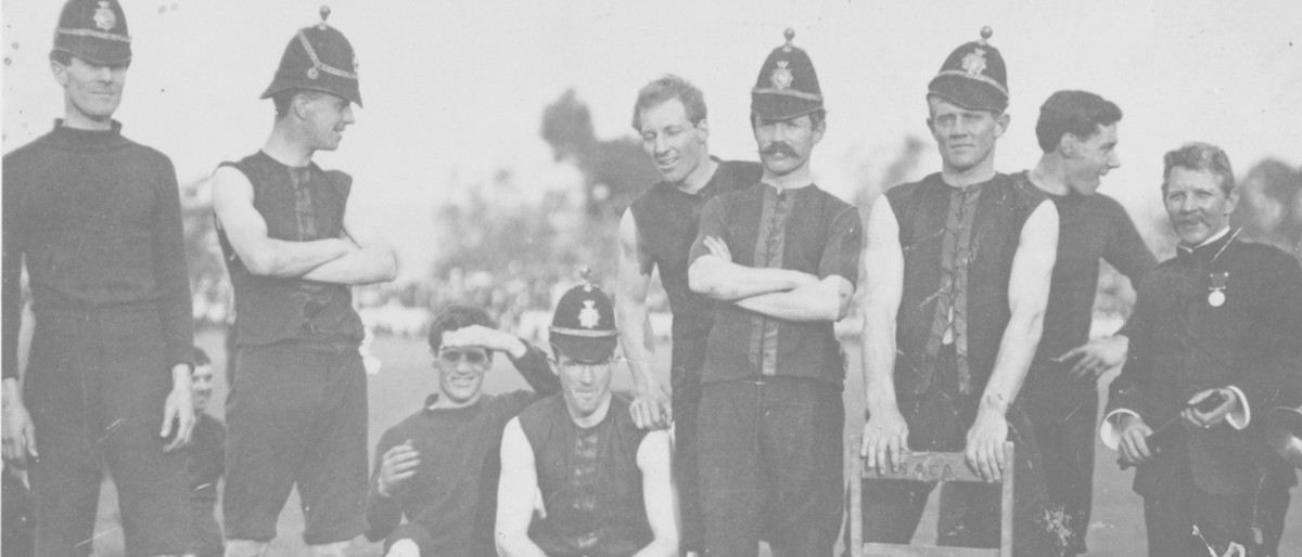 Image: A group of Australian Rules Football players in early twentieth century uniforms pose for a photograph. Most of the men are wearing period police helmets