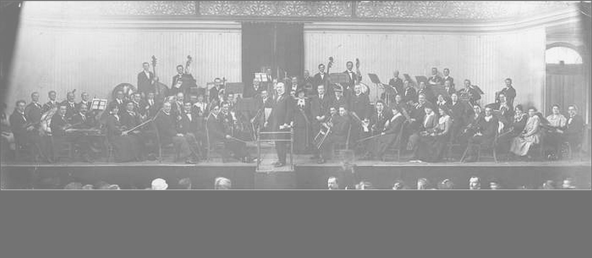 Image: A large symphonic orchestra is assembled on a stage at a large exhibition hall