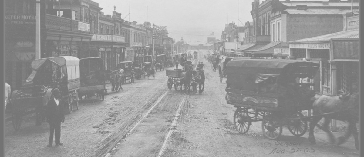 Image: horse drawn carriages on dirt city street