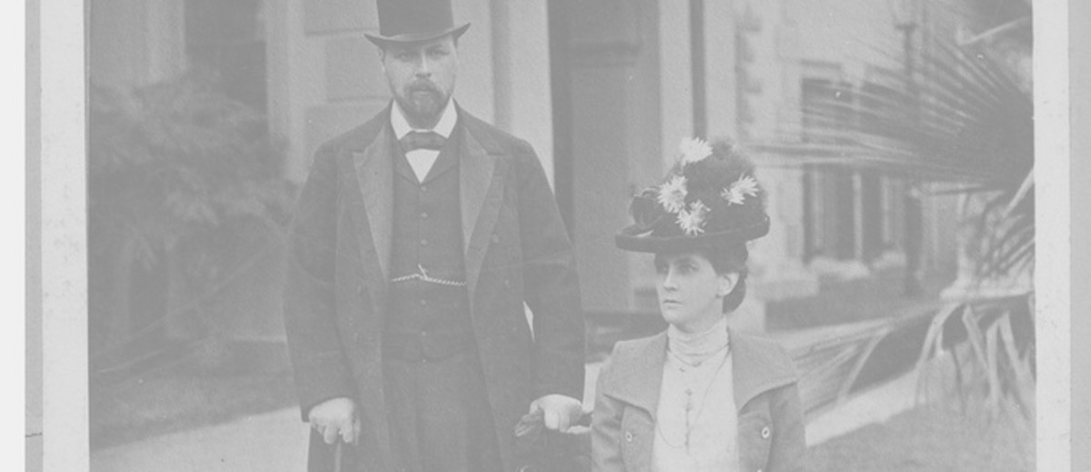 Image: Man in suit and top hat next to women sitting in dress and hat