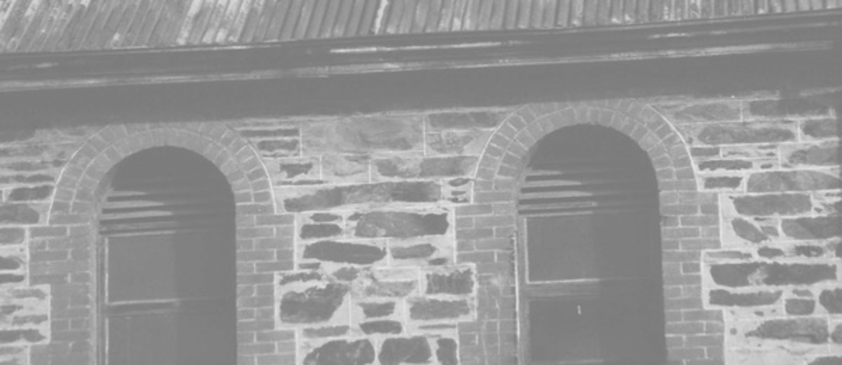 Image: Modern photograph of a bluestone building with arched windows surrounded in red brick and a rusty tin roof, topped with a weather vane.