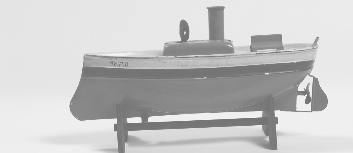 Image: toy boat made of metal and painted red, blue and cream