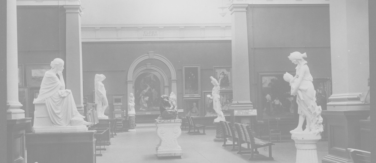 Image: The interior of an art gallery with high ceilings. Six white statues and numerous portrait paintings are in view