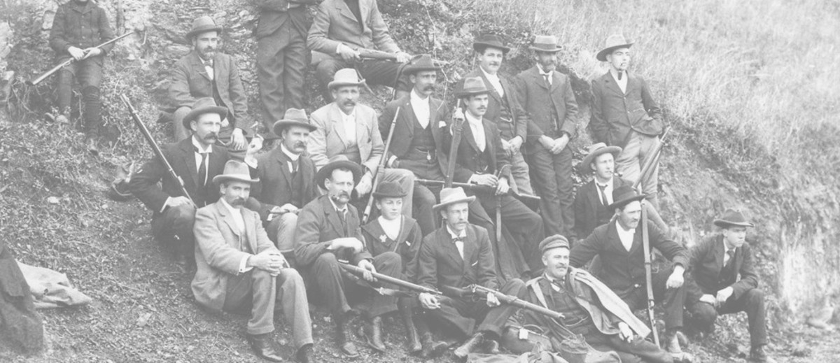 Image: Group of rifle club members sitting together on a hill holding rifles