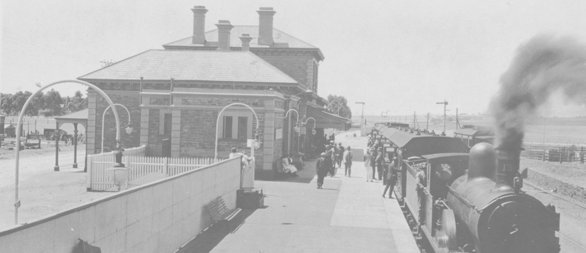 Image: A railway station. A train is on the platform to the right, with smoke coming out of the front. People are boarding the train. To the left is the station building, made of brick
