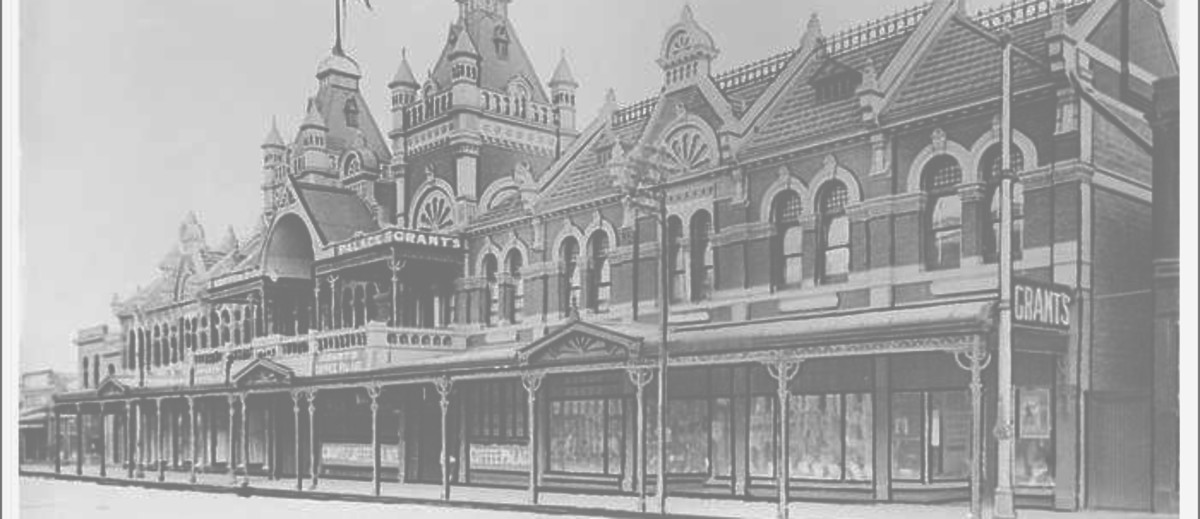 Image: a two storey ornate brick building with arched windows, a series of store windows beneath a verandah, two towers with square cupolas and flagpoles flying Australian flags above the main entrance and a tiled roof