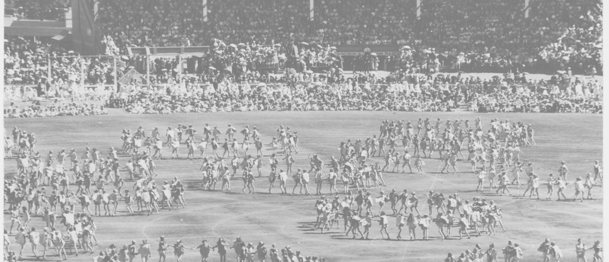 Image: An oval and grandstands filled with people, children dance on the oval in circular formations