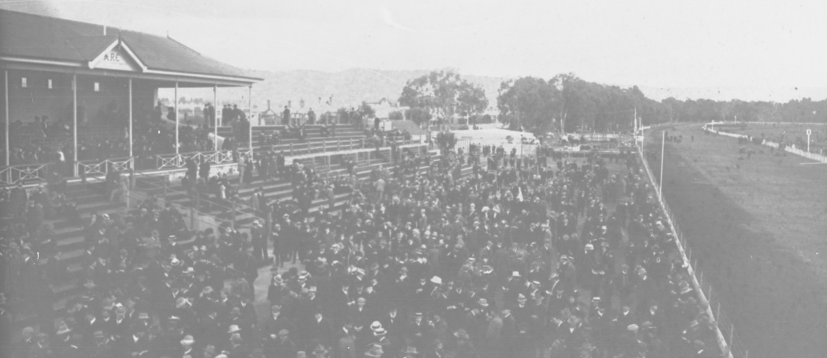 Image: large crowd of people at horse race track