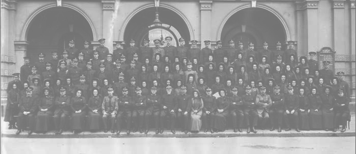 Image: A large group of people sit in rows outside the grand arched entrance of a large building, posing for a formal photograph. Three more people lean more casually on the balustrade of a balcony above.