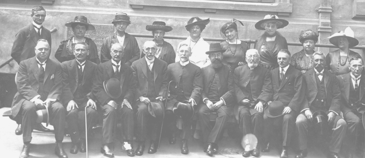 Image: Group of men and women sit and stand in two lines, most wearing dark clothing and hats