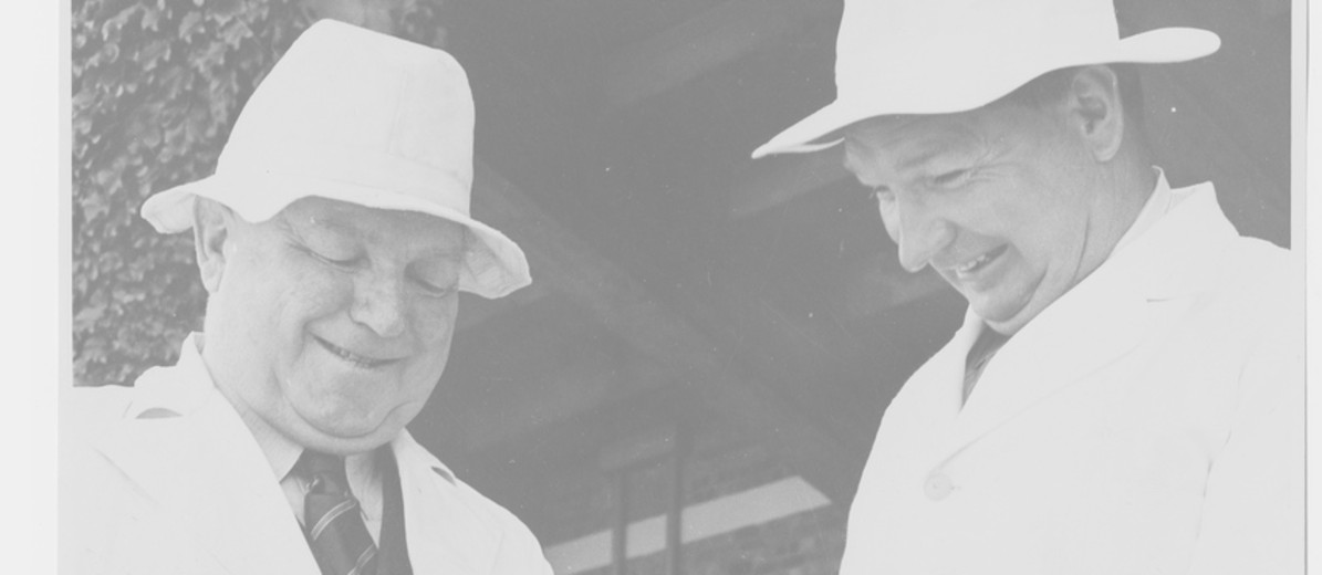 Image: Two men in white coats and hats smiling and engaging in conversation