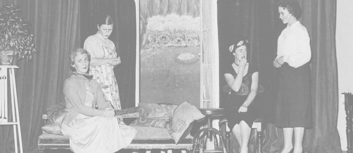 Image: Two women sitting, and two women standing on a stage with a dark curtain backdrop and various stage props