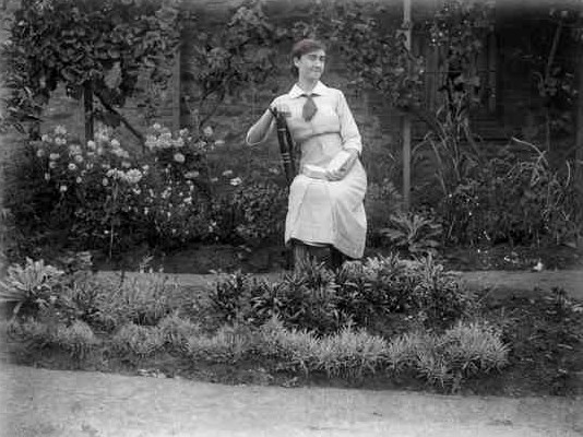 Image A Woman Holding Book Sits In Garden With Several Flowering And Other