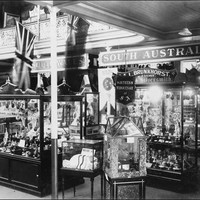 Image: A number of glass cabinets display a variety of items. Signs on the wall behind them reveal them to be items from New South Wales and South Australia.