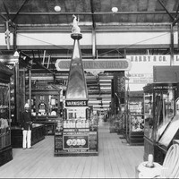 Image: a number of displays in glass cabinets fill a large hall. In the centre of the photograph a display of varnishes is topped by a pyramid. To the left a man stands in a uniform of a dark jacket and white pants and hat.