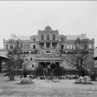 Image: A three storey building with a large external staircase leading down multiple terraces to a lawned area planted with trees and flowers. At various places on the staircase men stand in uniforms of dark coats and white pants.