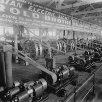 """Image: A display of 1880s """"electric light machinery"""" featuring wheels and belts in a large hall."""