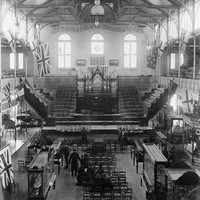 Image: a pipe organ takes pride of place at the far end of a large hall with a hammer beam roof. In the foreground men and women in black sit on rows of chairs surrounded by glass display cabinets.