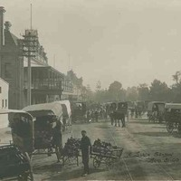 Image: A boy holding two hand-carts stands to the side of a busy street surrounded by horse-drawn carts. A tram line runs down the middle of the street, stone and brick buildings, one with a large balcony, line one side while the other fronts parklands.