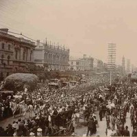 Image: a large crowd of people watch a contingent of soldiers in late 19th century military uniforms march down a wide city street led by four men on horseback