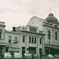 Image: a row of 1950s era cars are parked on a street outside of a row of two and three storey commercial buildings including a hotel with a verandah and balcony and a bank with a domed roof and flag pole.