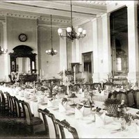 Image: a large dining room with multiple tables set with white cloths, candelabras and floral centrepieces.