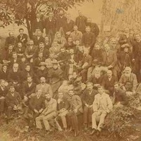 Image: a group of people gathered by a tree in a park