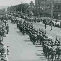 Image: men wearing Second World War era military uniforms and carrying rifles parade down a wide city street whilst crowds watch on from either side.