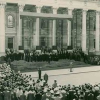Image: a man stands in front of a wide staircase leading up to a grand building with columns, photographing the men who are arranged upon it. A large crowd surrounds him.