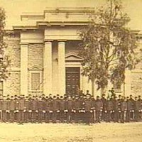 Image: a large group of men in 1860s police uniforms stand in front of a two storey stone building with columns flanking its entrance.