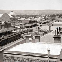 Image: a train is stopped in the centre of a city street which is lined with two and three storey buildings most of which have verandahs and one which features a large domed roof.
