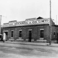 "Image: a single storey brick building with a low pitched roof behind a parapet sign reading ""Balfour, Bricknell & Co. Ltd. Cake Specialists"". To the right is a corrugated iron building with part of a sign visible reading ""South Aust"""
