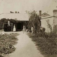 Image: A family (a man, woman, three boys and two girls) and their dog pose in an overgrown garden outside a single storey cottage with verandah.