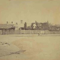Image: fruit trees, tin roofs and brick chimneys rise above a paling fence bordering a dirt road. A number of people in late 19th century dress can be seen standing in front of the fence.