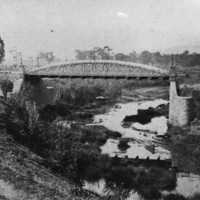 Image: a bridge with an arched parapet spans a small river in a deep valley